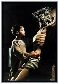 niño delante del crucifijo
