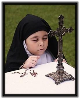 Niña con hábito de Carmelita en oración