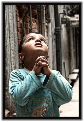 Niño rezando mirando al Cielo