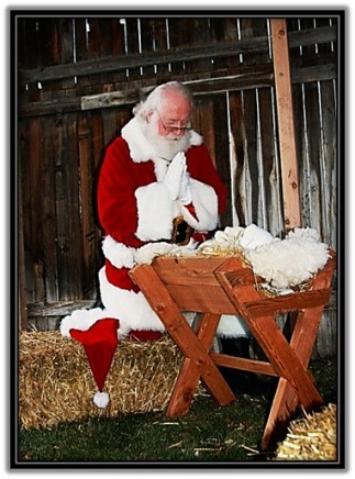 Papa Noel arrodillado ante el Niño Jesús